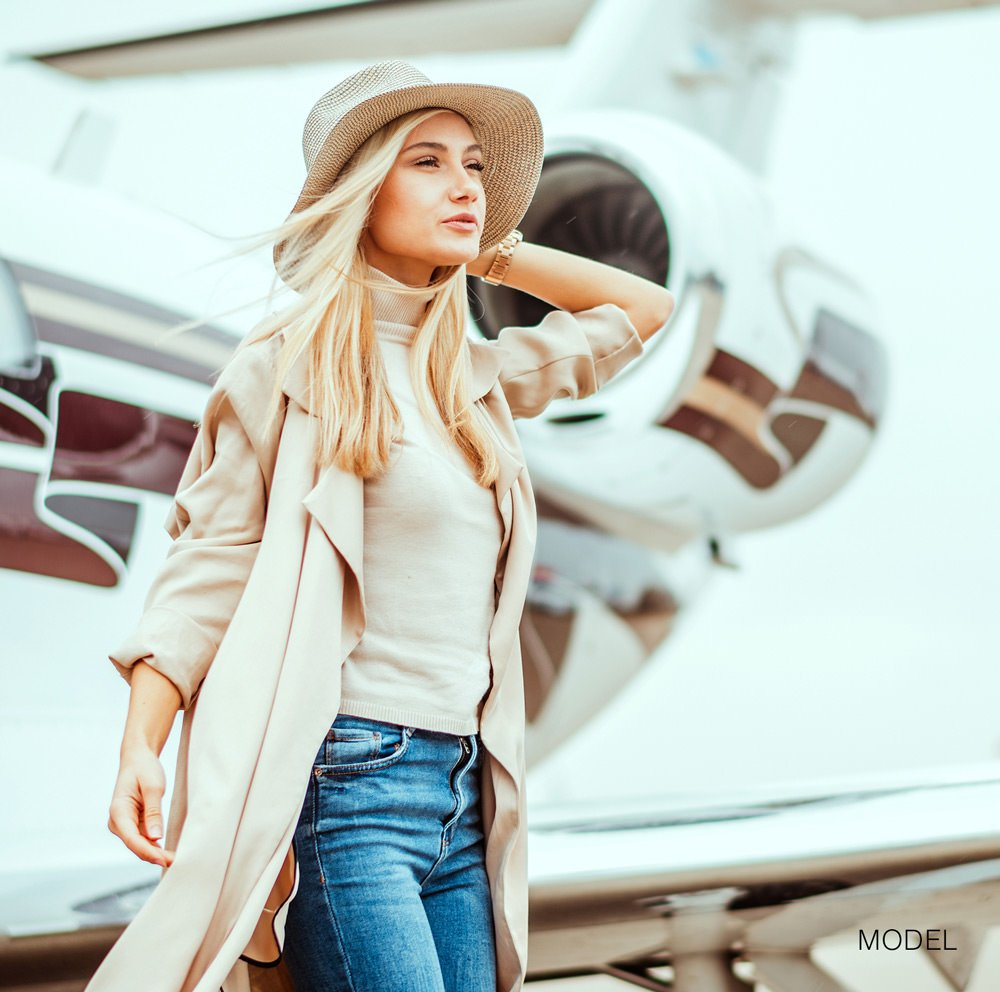 Model walking in front of a private jet